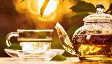 Teatime on sunset background. Health drink black herbal tea in a glass cup