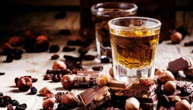 Milk chocolate and hazelnuts surrounding glasses of rum