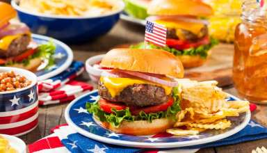 Beef burger with crisps (potato chips) and an American flag stuck in the burger bun