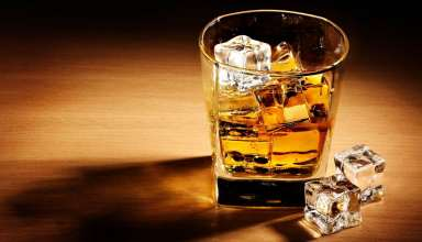 A glass of whisky with ice cubes inside
