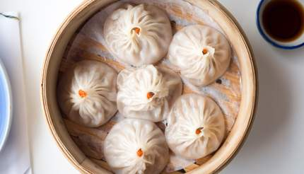 Xiao long bao steamed buns in a small bamboo basket