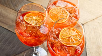 aperitif with ice and a slice of orange in large round glasses