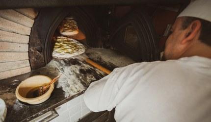 A baker making schiacciata, a type of flatbread