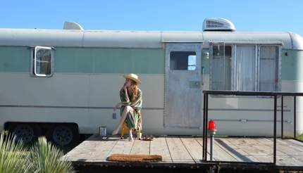Woman sitting outside trailer at El Cosmico