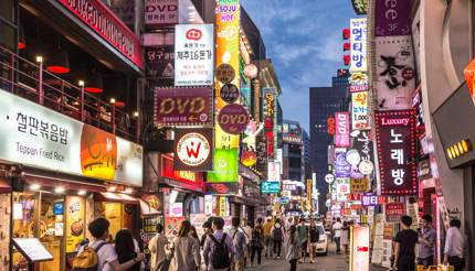 Busy street lined with restaurants in the Myeong-dong district at night